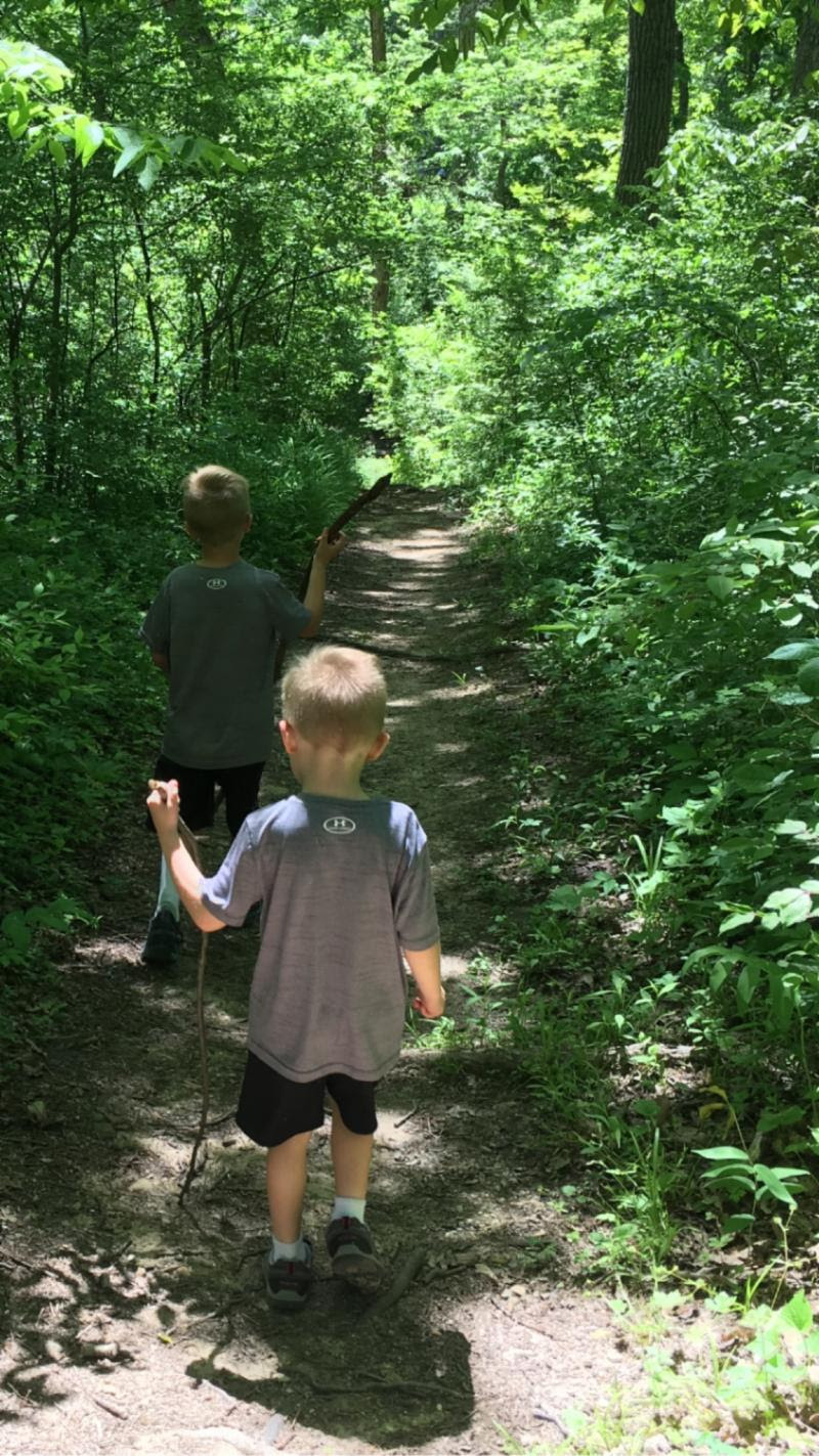 image of two children walking on a path in the woods